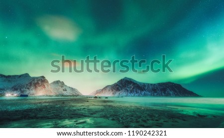 Northern lights above the rocks in Lofoten islands, Norway. Aurora borealis. Starry sky with polar lights and clouds. Night winter landscape with aurora, sea, beach and snowy mountains. Travel #1190242321