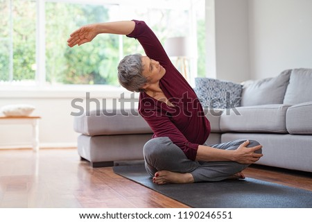 Senior woman exercising while sitting in lotus position. Active mature woman doing stretching exercise in living room at home. Fit lady stretching arms and back while sitting on yoga mat. #1190246551