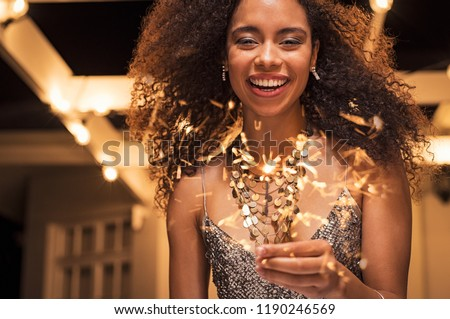 Portrait of young african girl holding sparkle stick under the patio outdoor. Happy smiling woman celebrating with fireworks. Elegant woman holding a bengal light for new year's eve party. #1190246569