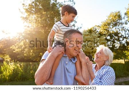 Grandparents Giving Grandson Ride On Shoulders In Summer Park Against Flaring Sun #1190256433