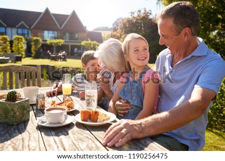 Grandparents With Grandchildren Enjoying Outdoor Summer Snack At Cafe #1190256475