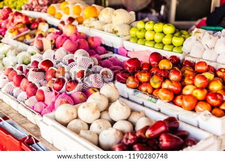 A traditional Thai market stall selling apples and other tropical fruits #1190280748
