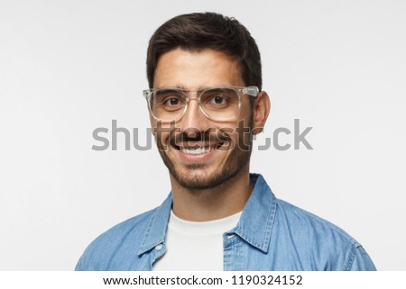 Closeup headshot of smiling young man in blue shirt against gray background, wearing transparent spectacles #1190324152