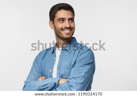 Handsome young man isolated on gray background, dressed in casual blue shirt, having turned aside as if looking at something