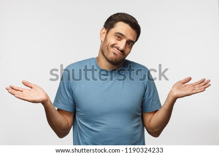 I don't know. Young man isolated on gray background, showing helpless gesture with arm and hands, mouth curved as if he does not know what to do #1190324233
