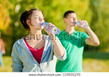 Man and woman drinking water from bottle after fitness sport exercise #119035270