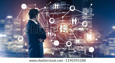 Thoughtful businessman against night cityscape working with social connection media concept #1190395288