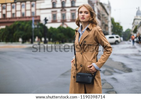 Young attractive woman in trench coat with little black cross bag dreamily looking in camera spending time on cozy city street #1190398714