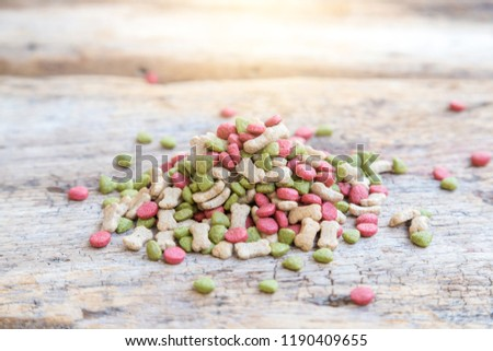 Puppy Dog food 3 mix. Pile of puppy dog food on wooden table. Puppy dog food bone shape, round shape and triangle shape. #1190409655