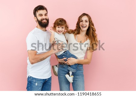 A happy family on pink studio background. The father, mother and son posing together
