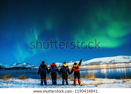 Group Tourists visiting in Tromso. Amazing beautiful Aurora, also know as Northern Lights dancing over the night sky. Travel, tourism, holidays concept. #1190418841