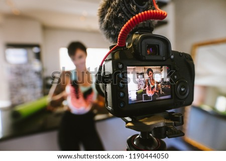 Female vlogger holding sports shoes in hands happily looking in camera while recording video for blog. Focus on camera with social media influencer reviewing and marketing a sports shoe. #1190444050