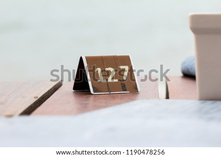 """Double-Sided Triangle Vintage Metal Table Sign of Number """"127"""" on Wooden Table with Blurred Background #1190478256"""