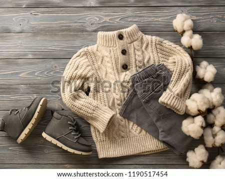 Fashion children's clothing, shoes (knit sweater, jeans, suede boots). Outfit for little boy. Winter, autumn collection. Organic cotton. Top view, flat lay