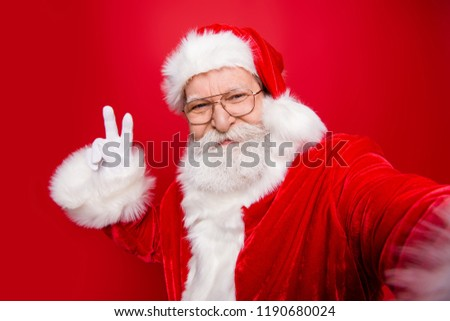 Kind cheerful positive mature Santa with white beard in costume headwear gloves stylish spectacles show v-sign take noel self picture on camera of smartphone isolated on red background