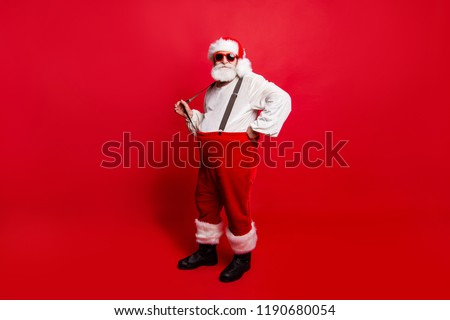 Full length body size of nice calm peaceful Santa pulling suspender preparing to feast festive party promo sale discount isolated over red background #1190680054