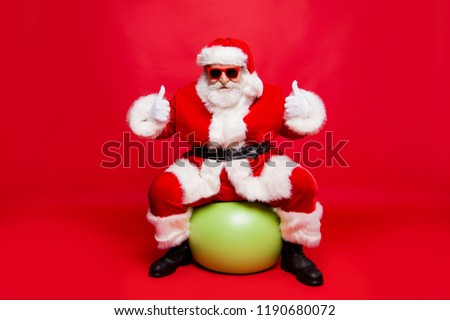 Funny cheerful positive stylish Santa in eyeglasses white fluffy gloves fur coat winter belt outfit sitting on pilates ball prepared ready for sale promo discount isolated over red background fun joy #1190680072