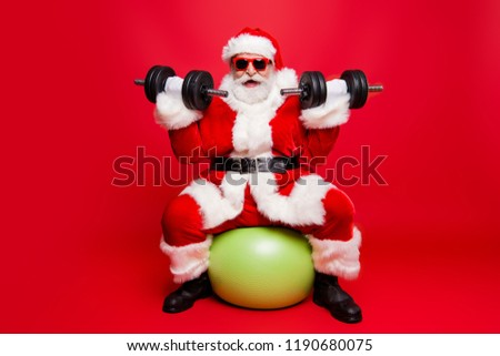Cheerful sporty muscular virile strong Santa in white fluffy gloves fur coat sitting on pilates ball work out ready for sale promo discount wishing merry x mas isolated on red background fun joy #1190680075