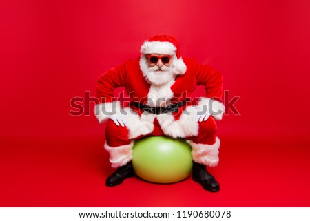 Funny positive stylish fashionable Santa in eyeglasses gloves fur coat winter outfit black belt sitting on green ball prepared ready for sale promo discount isolated over red background #1190680078