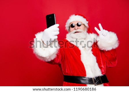 Stylish trendy grandfather aged mature Santa tradition winter costume headwear spectacles white beard take christmastime selfie picture front camera show v-sign isolated red noel eve background