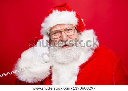 Stylish Saint Nicholas with white beard in eyeglasses costume headwear answer talk on the phone isolated on red background look at camera #1190680297