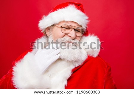 Aged mature stylish confused moody frustration grandfather Santa in costume glasses touch hand gloves to cheek make isolated on red background #1190680303