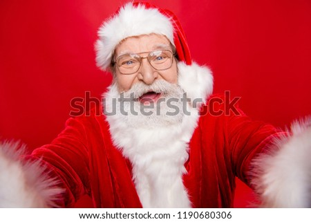Cheerful happiness careless carefree stylish positive glad aged grandfather Santa take self picture on front camera of modern smartphone isolated on noel red background make beaming toothy smile #1190680306