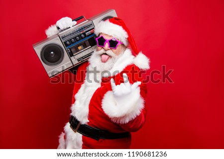 Heavy metal winter noel wish funky mood mature aged senior Nicholas white beard in costume headwear gloves stylish star glasses show tongue out hold vintage record player isolated on red background #1190681236