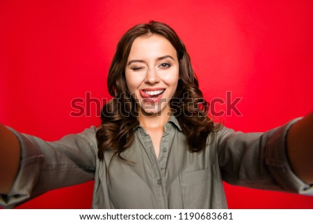 Close up portrait beautiful, attractive, pretty, dreamy, lady with curly hairstyle, take selfie on front camera of modern smartphone, wear in casual blouse wink eye isolated on shine red background