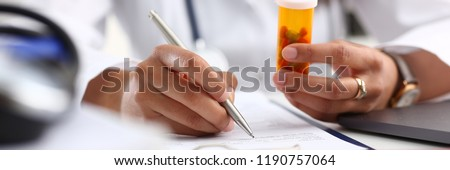 Female black medicine doctor hand hold jar of pills and write prescription to patient at worktable. Panacea and life save, prescribing treatment legal drug store concept. Empty form ready to be used #1190757064