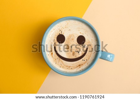 Cup of delicious hot coffee with foam and smile on color background, top view. Happy morning, good mood, inspiration #1190761924
