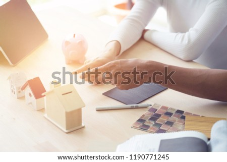 Happy couple plan buying house.Concept for Couple saving money for buy home and real estate. Select material for decorate furniture. #1190771245