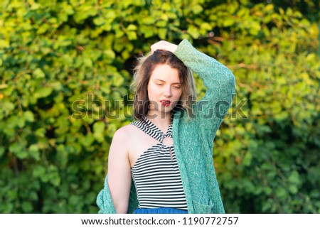 portrait of a beautiful girl in a park standing in a green jacket #1190772757