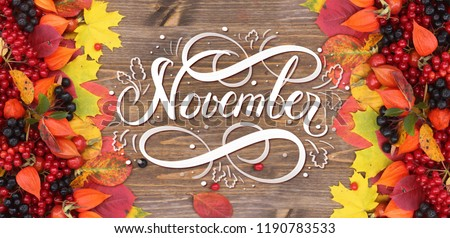 November hand lettering inscription. Bright red autumn leaves and berries frame composition on old wooden background. Great season texture with fall mood. Nature november background.  Royalty-Free Stock Photo #1190783533