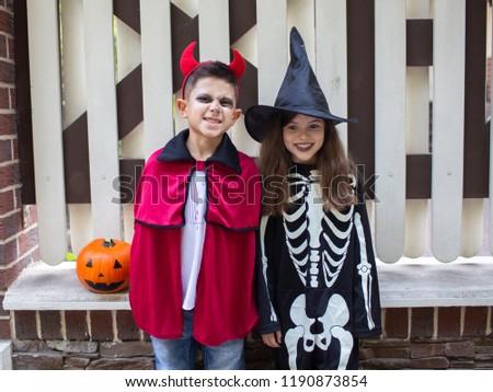 Cheerful children in halloween costumes celebrating halloween with pumpkins. Halloween concept. #1190873854