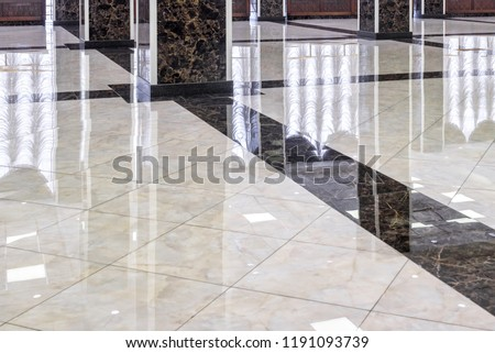 Marble floor in luxury lobby of office or hotel. Clean floor tile with reflections for background. Shiny stone floor in commercial building after professional cleaning service. Royalty-Free Stock Photo #1191093739