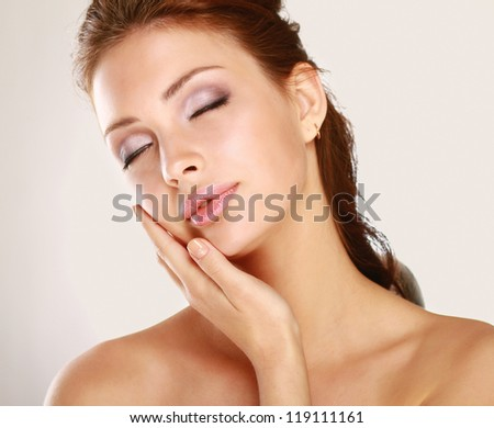 Young woman touching her face isolated on whire background #119111161