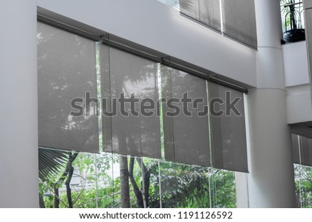 Close up luxury Long blind, curtain, roller, shade, shutter protected sunlight with large glass wall and blur green tree background. Royalty-Free Stock Photo #1191126592