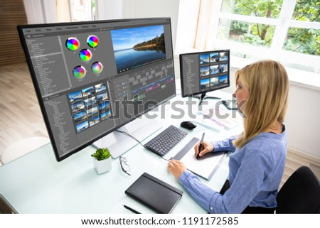 Female Editor Using Graphic Tablet While Editing Video On Computer #1191172585