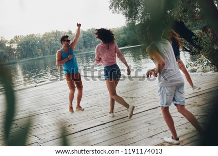 Sincere fun. Full length of young people in casual wear smiling and having fun while standing on the pier  #1191174013