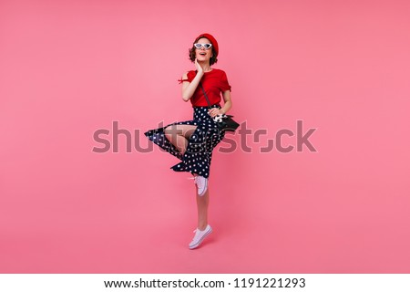 Full-length portrait of cheerful well-dressed girl having fun in studio. Debonair french lady with short brown hair dancing on pink background. #1191221293