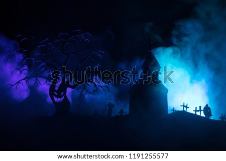 Scary view of zombies at cemetery dead tree, moon, church and spooky cloudy sky with fog, Horror Halloween concept. Toned #1191255577
