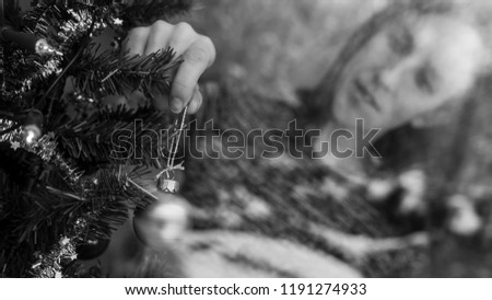 Monochrome image of a young woman hanging holiday bauble on Christmas tree. View through a window. #1191274933