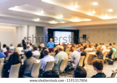 Blurred business seminar meeting with LED projector screen and speaker speech on stage. Defocused rear view audience in conference hall room, listening talk show in USA. Education, business concept #1191317806