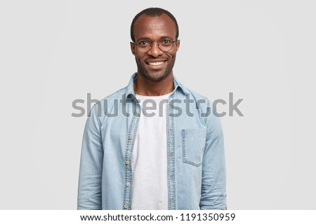 Waist up shot of handsome self confident cheerful male entrepreneur has broad smile, wears round transparent glasses, happy to meet with colleague, dressed in fashionable denim shirt isolated on white #1191350959