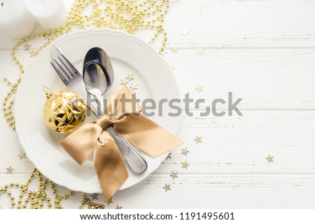 Festive place setting for christmas dinner on white rustic background. Christmas table setting with gold decorations on wooden table. Holiday Decorations. Top view. Copy space. #1191495601