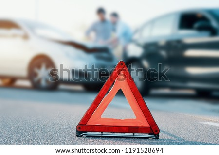 Two men reporting a car crash for the insurance claim,main focus on red triangle Royalty-Free Stock Photo #1191528694