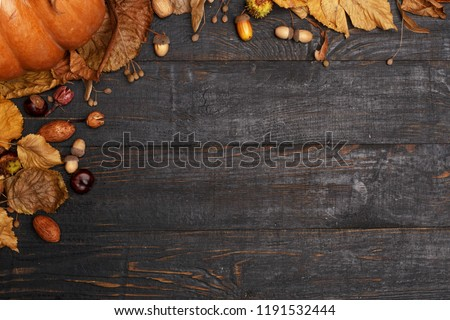 Autumn composition with dry leaves and ripe pumpkins on a dark wooden table. Top view. Copy space #1191532444