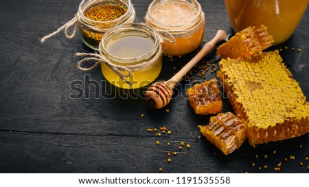 A set of honey and bee products. Honey in honeycomb. On a black wooden background. Free space for text. Top view. #1191535558