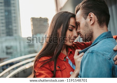 Side view calm lady hugging orderly handsome man while telling with him during leisure outdoor #1191548701